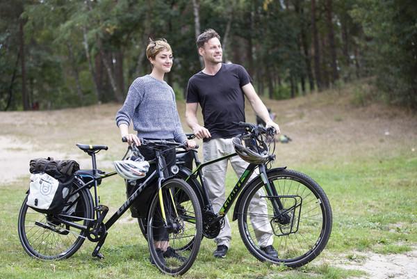 Zwei Radfahrer schieben ihr Rad