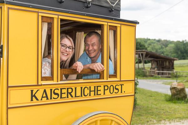 Ein Wanderpaar ist in der Tecklenburger Postkutsche unterwegs.
