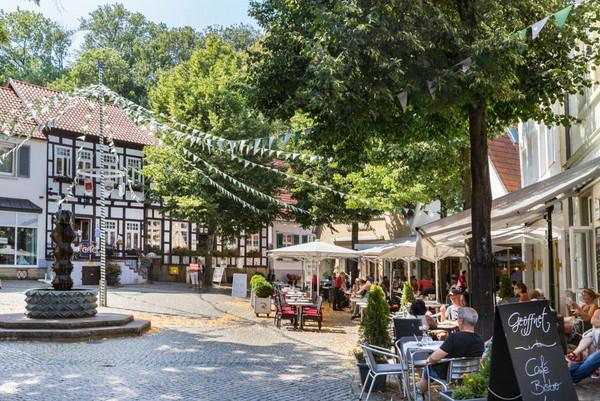 Am Marktplatz von Tecklenburg sind viele Cafés, ein Brunnen und Fachwerkhäuschen.