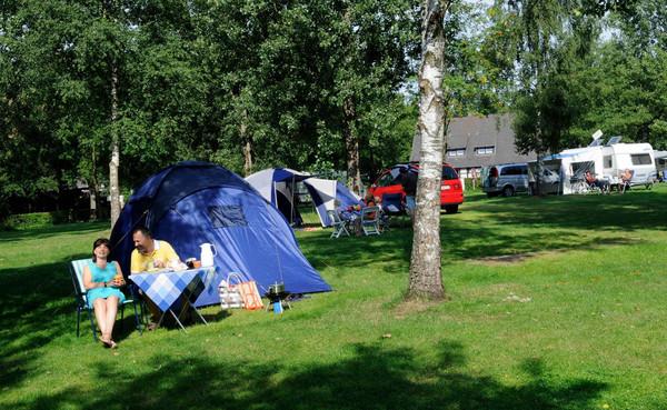 Ein Zelt steht auf der Wiese, zwei Camper sitzten davor
